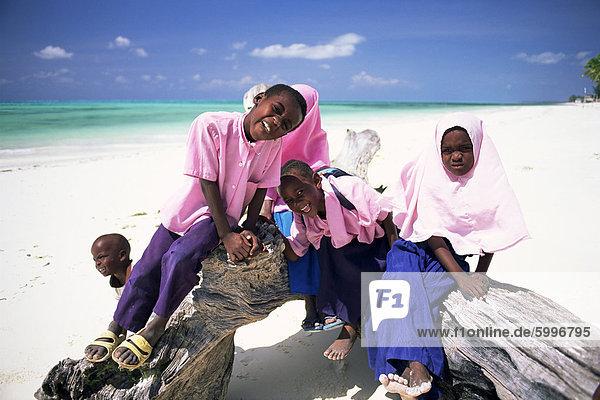 Young Muslim children in school uniform on beach at Jambiani  Zanzibar  Tanzania  Africa