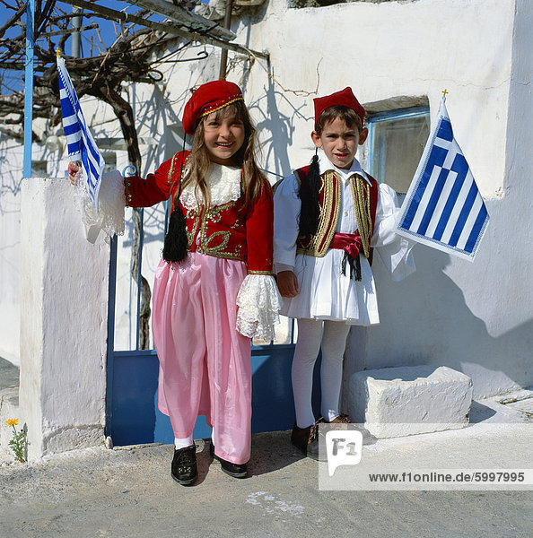 Portrait of two children in national dress carrying flags  celebrating Independence Day  in Greece  Europe
