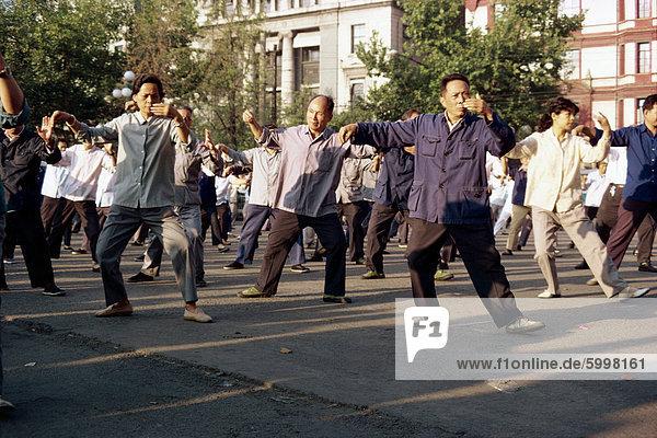 Eine Gruppe von Männern und Frauen Tai-Chi-Übungen an der frischen Luft auf dem Bund in Shanghai  China  Asien