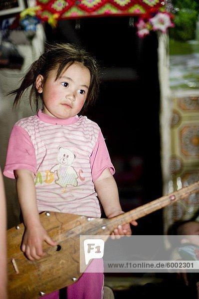 Ein junges Mädchen spielt die Dombra in Bayan Ölgii  Mongolei  Zentralasien  Asien