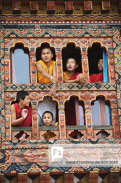 Young monks at a window  Chimi Lhakhang dating from 1499  Temple of the Divine Madman Lama Drukpa Kunley  Punakha  Bhutan  Asia