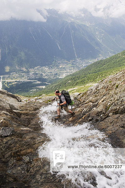 Hiker crossing a stream above Chamonix Valley  Rhone Alps  France  Europe