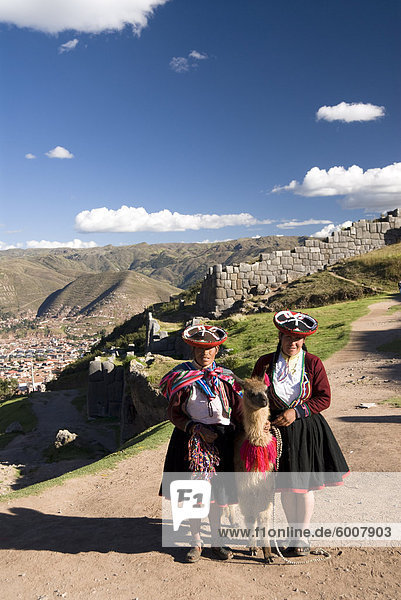 Inca Frauen in traditioneller Kleidung und Lamas  mit der Festung von Sacsayhuaman im Hintergrund  in der Nähe von Cuzco  Peru  Südamerika