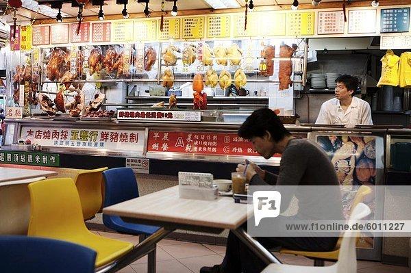 Mann im Café mit hängenden gebratene Ente und Schweinefleisch und chinesische Menüs  Hong Kong  China  Asien