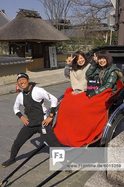 Rikscha Fahrer und zwei junge japanische Frauen in Rikscha mit roter Decke winken in die Kamera  Maruyama-Park  Higashiyama-Viertel  Kyoto  Kansai  Honshu  Japan  Asien