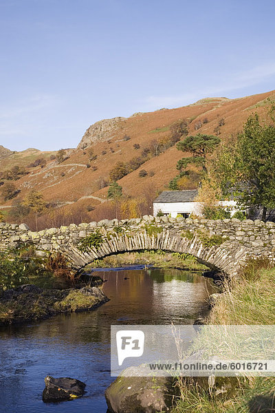 Alte steinerne Packhorse Brücke über den Watendlath Beck im malerischen Dorf im Herbst  Watendlath  Lake District-Nationalpark  Cumbria  England  Vereinigtes Königreich  Europa