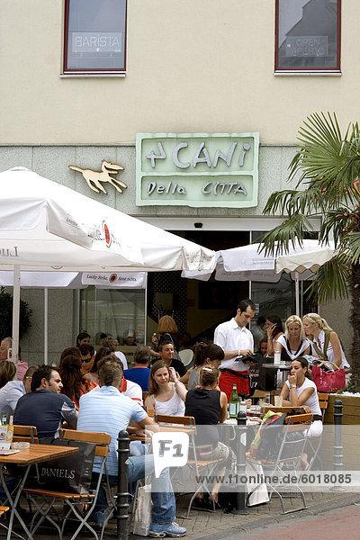 Leute sitzen außerhalb der beliebten 4 Cani Della Citta-Café am Benesis Strasse  Köln  Nord Rhein Westfalen  Deutschland  Europa