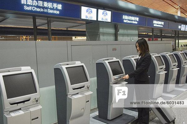 Eine chinesische Business-Frau mit den Self-Service check-in Maschinen am Beijing Capital Airport Teil des neuen Terminal 3 Gebäude eröffnete Februar 2008  zweitgrößte Gebäude der Welt  Peking  China  Asien