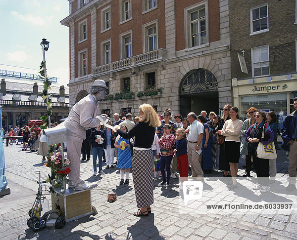 Statue street performer  and group of people watching  Covent Garden  London  England  United Kingdom  Europe