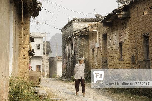 Frau zu Fuß durch Dorf Straßen  Yangshuo  Provinz Guangxi  China  Asien