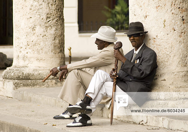 Zwei kubanische Männer Jahrgang der 40er Jahre Kleider und Rauchen von Zigarren während des Wartens auf touristischen Fotografen in Plaza De La Catedral  Habana Viejo  Havanna  Kuba  Westindische Inseln  Mittelamerika