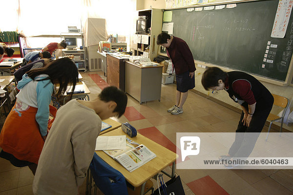 Students bowing to teacher in class  elementary school  Tokyo  Honshu  Japan  Asia