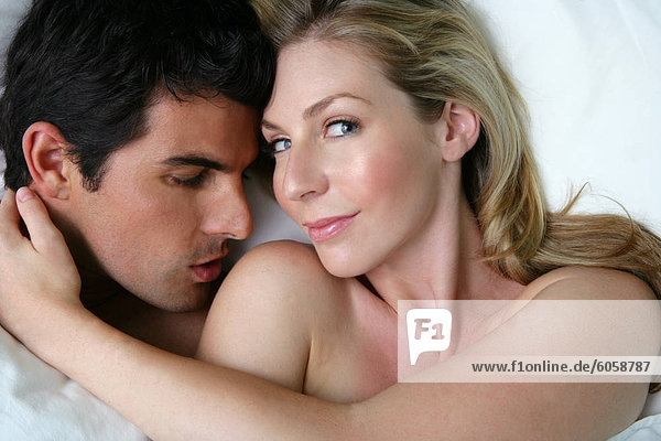 Junger Mann küssen Frau Schulter im Bett.