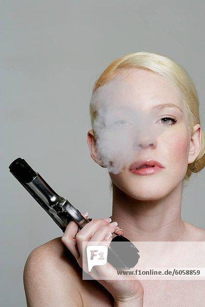 Frau hält eine Waffe und Ausblasen Rauch