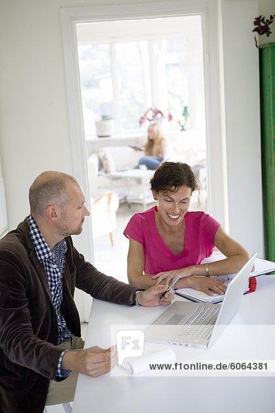 Mann und Frau auf Laptop arbeiten