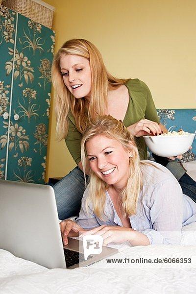 Zwei junge Frauen mit Laptop im Schlafzimmer