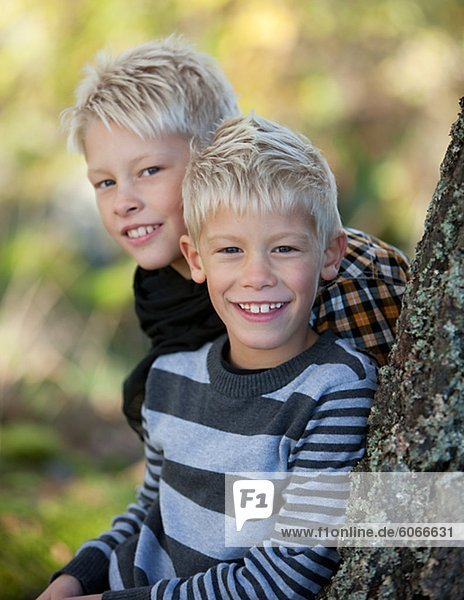 Portrait of two blonde boys leaning against tree trunk