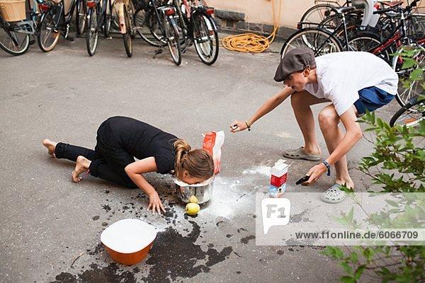 Kinder spielen mit dem Essen auf Bürgersteig