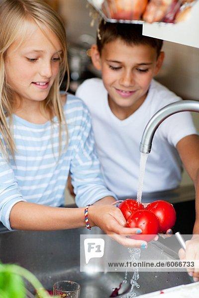 Ein Junge und ein Mädchen Tomaten vorbereiten