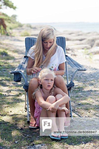 Teenager-Mädchen machen Zöpfe zu ihrer Schwester
