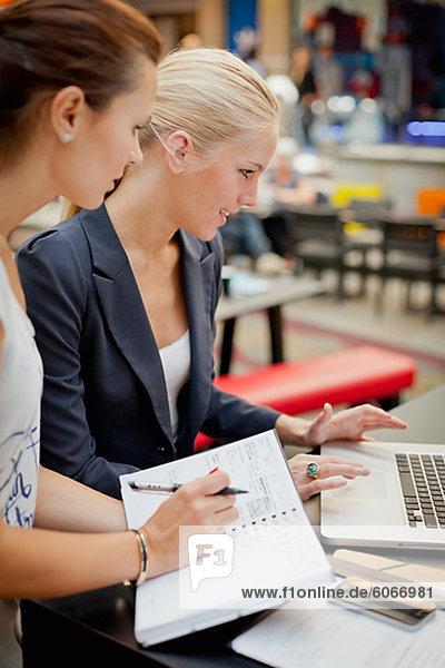 Zwei junge Frauen  die Arbeiten mit laptop