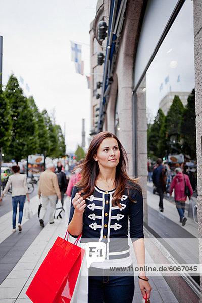 Frau mit Einkaufstasche Wandern in Strasse