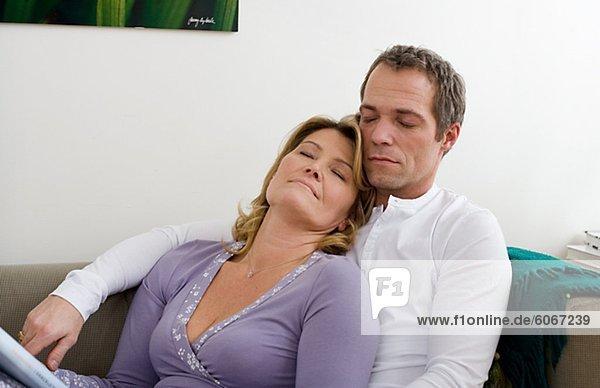 Mitte adult Paar auf Sofa sitzend