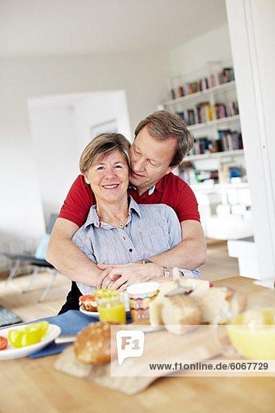 Ältere paar umarmen während des Frühstücks