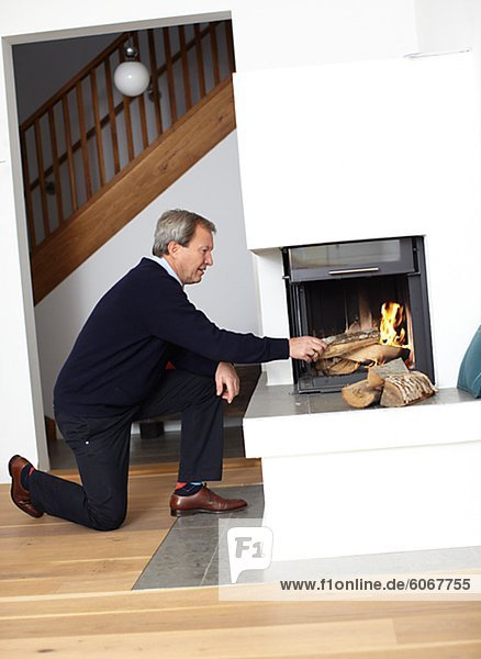Mature man putting fire wood into fire place