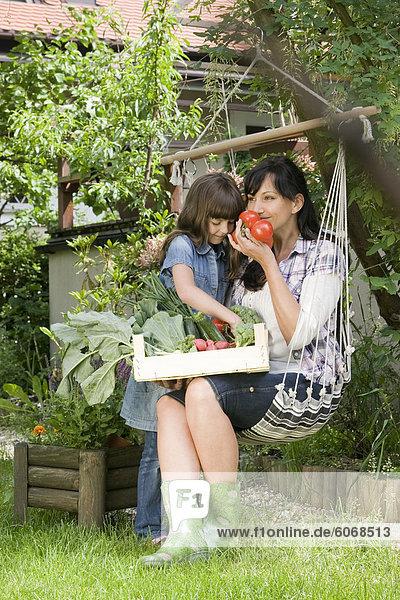 Mutter mit Tochter Blick auf frischem Gemüse im Garten