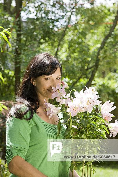 Frau trägt Topfblumen