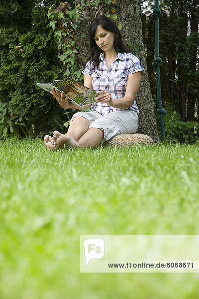 Woman reading magazine in garden