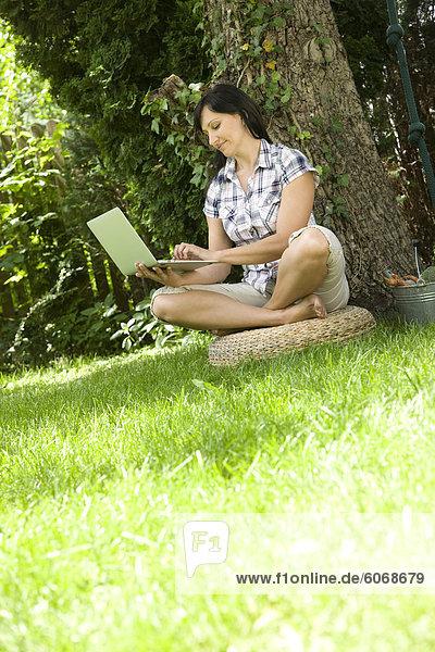 Woman using notebook in garden