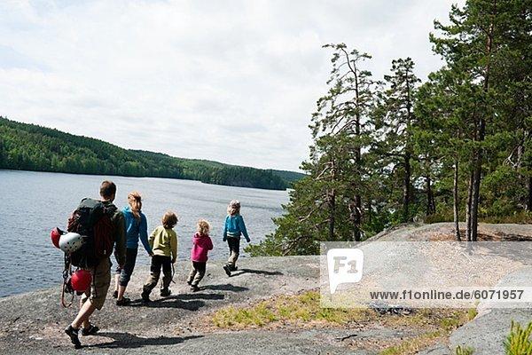 Familie mit vier Kindern Seeufer entlang