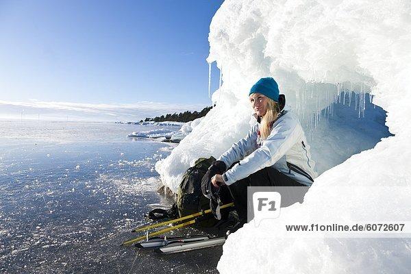 Frau sitzt auf dem Eis  Lächeln