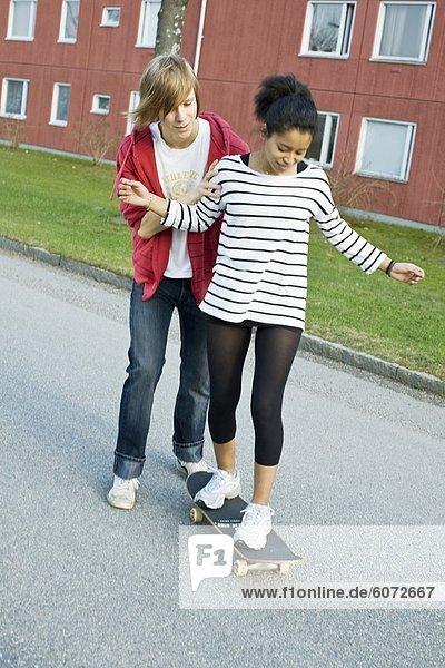 Teenager  die Unterstützung von Mädchen auf skateboard