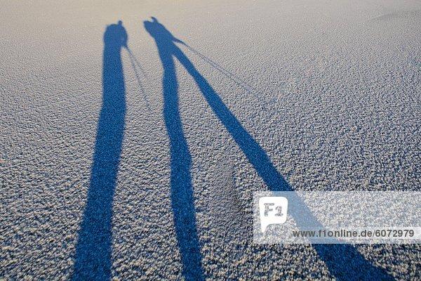 Schatten zweier Menschen auf dem Eis