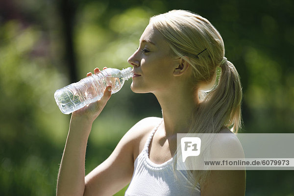 Eine junge Blondine  trinken eine Flasche Wasser  Nahaufnahme