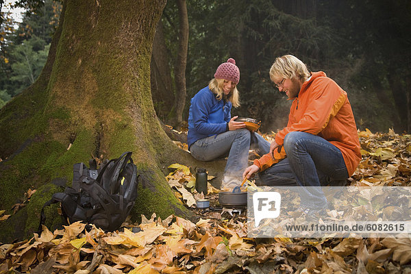 Couple cooking lunch in the woods.