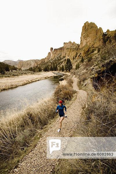 A woman in bright colors jogging near a river.
