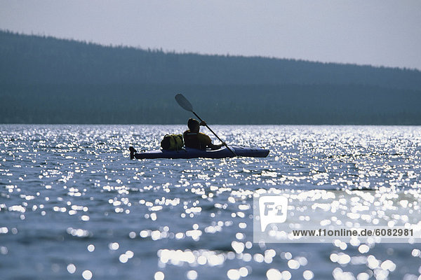 Female sea kayaker backlit by the sun on a lake in Canada.