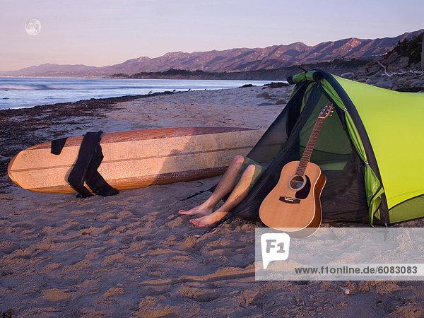 liegend liegen liegt liegendes liegender liegende daliegen Mann Strand warten camping Zelt Gitarre jung Brandung