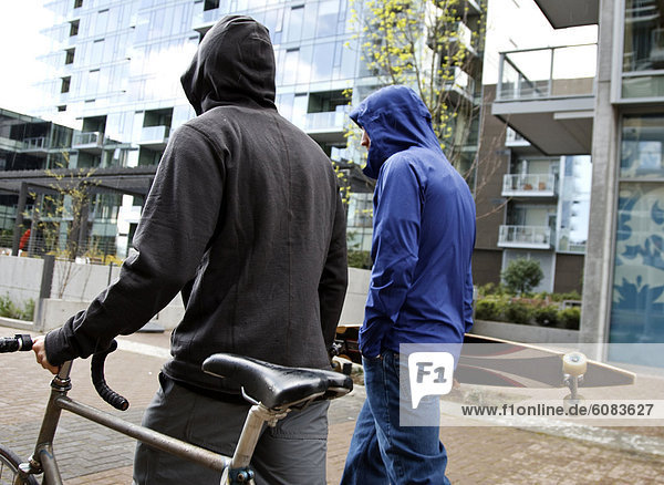 Two men walking in a light rainstorm with their hoods up pushing a bike.