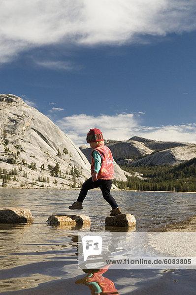 A toddler girl stepping on rocks at Tenaya Lake  Yosemite National Park  California.