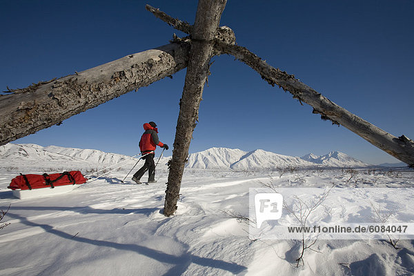 A woman hiking through a snowy  mountainous landscape pulling a sled.