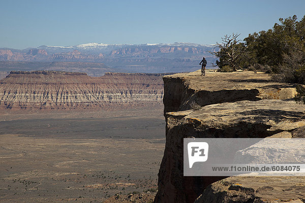 A woman mountain biking near the edge of a cliff near Hurricane  Utah.