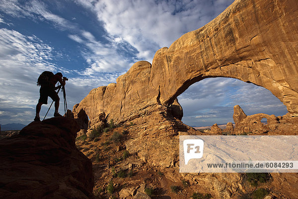 A silhouette of a photographer looking through his camera on a tripod while taking a photo of an arch in Arches National Park  Utah.