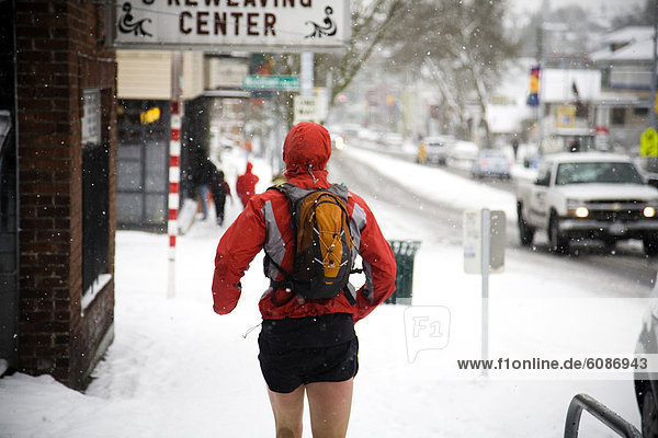 A male runner with a backpack runs down a city street while wearing shorts in the winter.