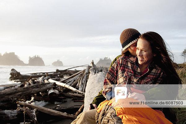 Mann Fröhlichkeit geben Ehefrau schieben Strand Sonnenuntergang küssen dahintreibend