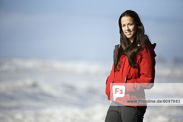 A woman smiles at the camera while watching ocean waves in a turbulent sea.